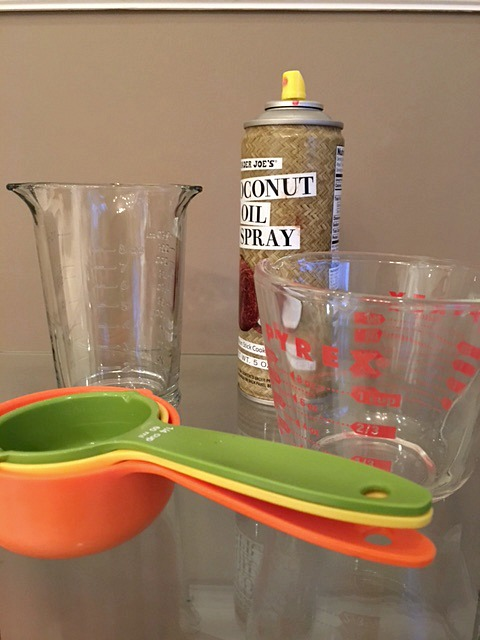 Spraying Measuring Cups with Cooking Spray